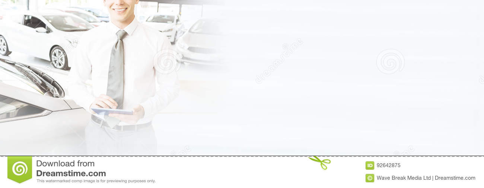 Smiling salesman using tablet near a car
