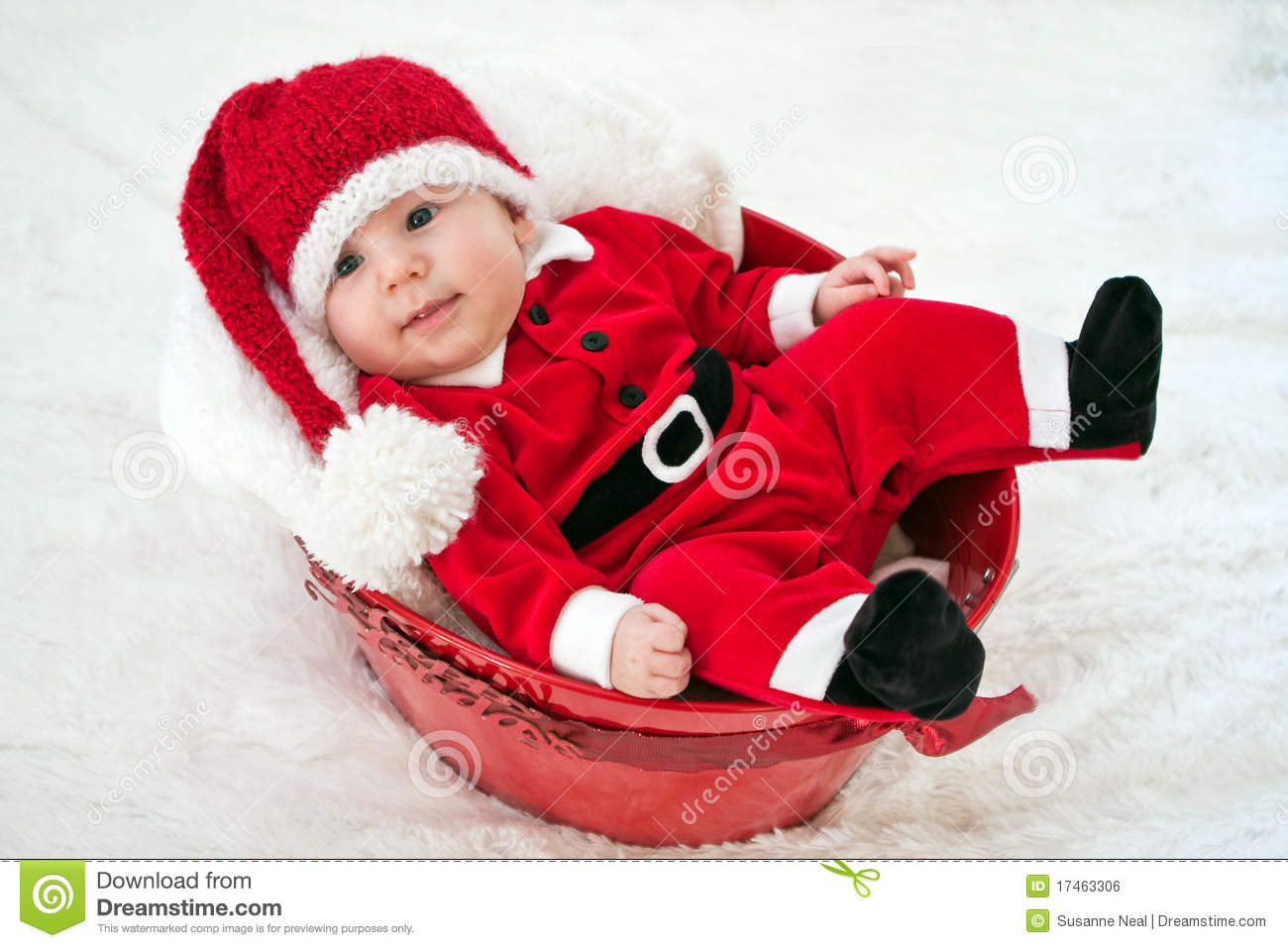 fb8a97b7e A cute four month old baby wears a red Santa suit and knitted cap. He has  bright blue eyes and an adorable big smile. He is lying comfortably in a  red ...