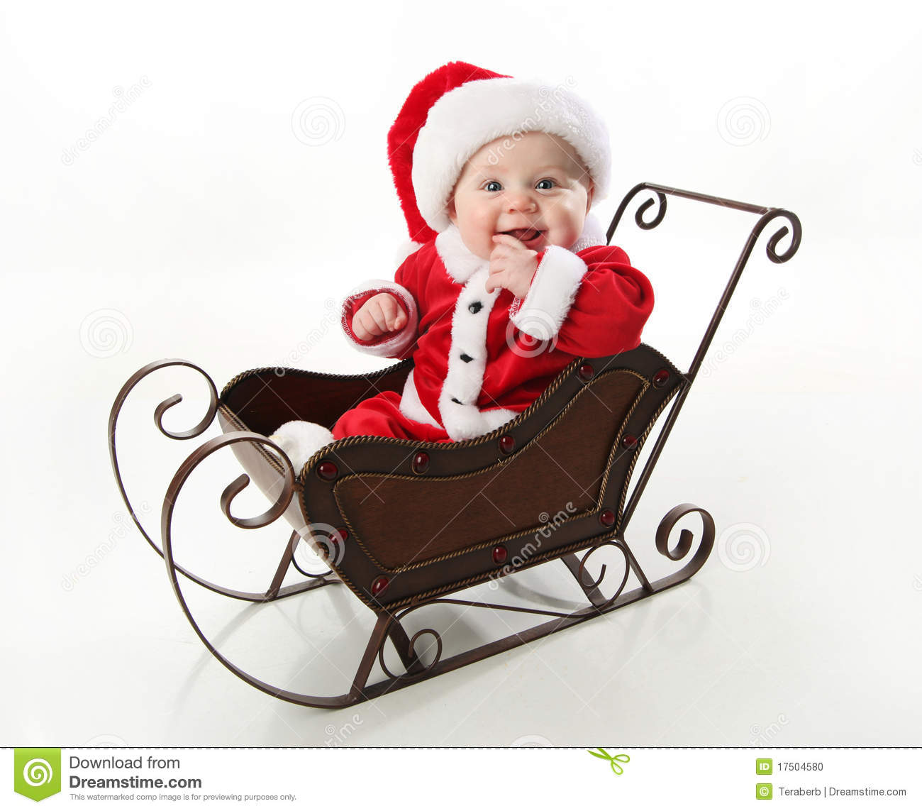 Smiling Santa Baby Sitting In A Sleigh Stock Photo