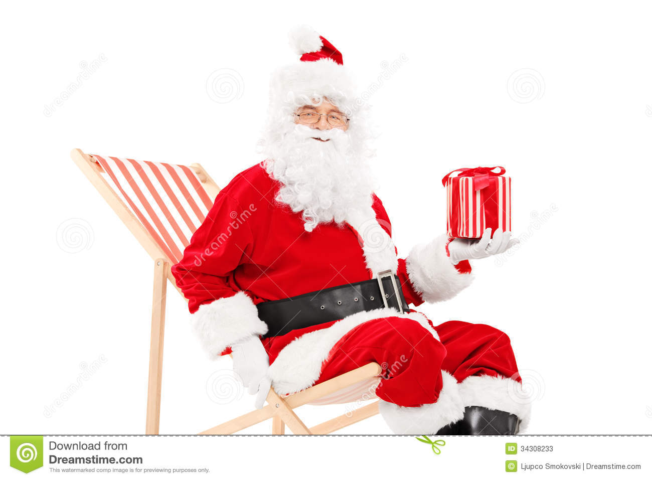 Smiling Santa Claus sitting on a beach chair and holding a gift