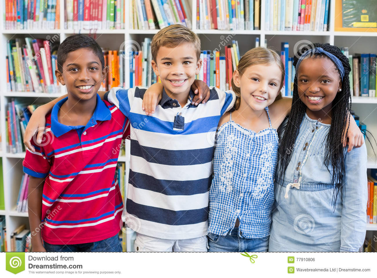 Smiling school kids standing with arm around in library