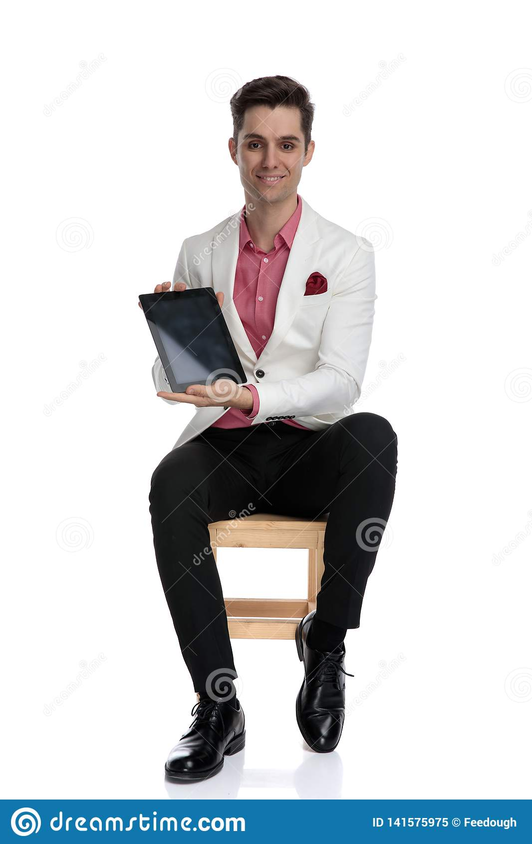 Smiling seated businessman showing blank screen of a tablet