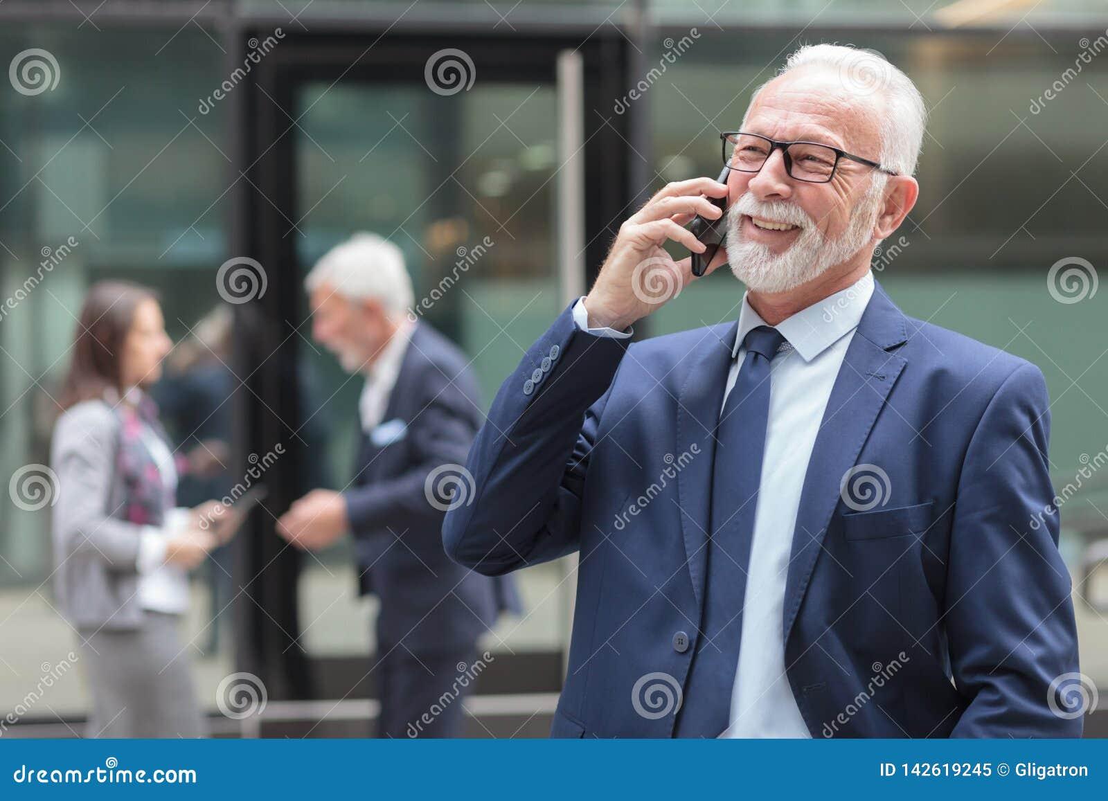 Smiling senior businessman talking on the phone on the street