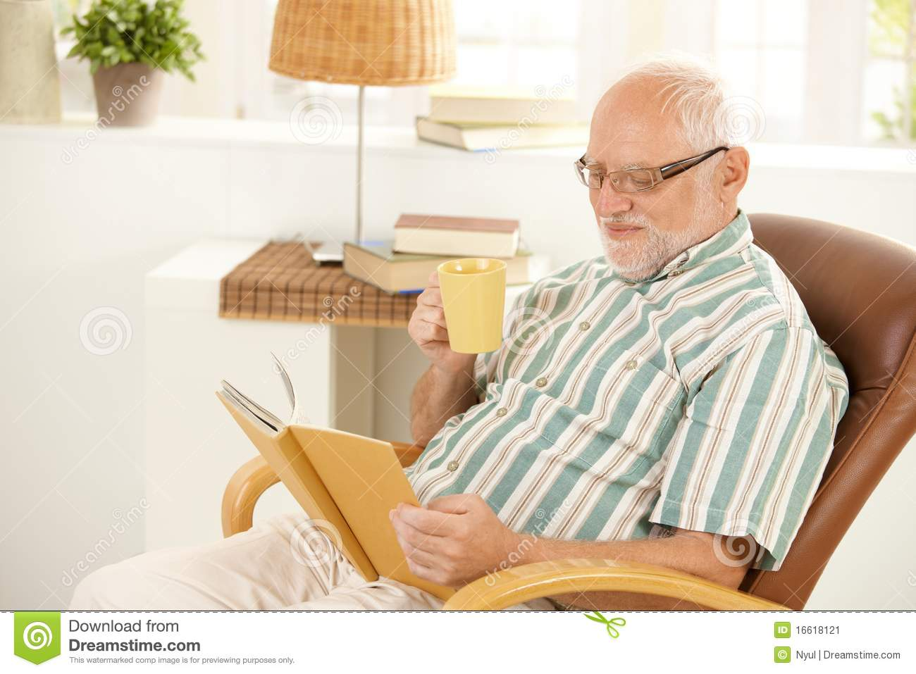 Smiling Senior Relaxing At Home With Book And Tea Stock