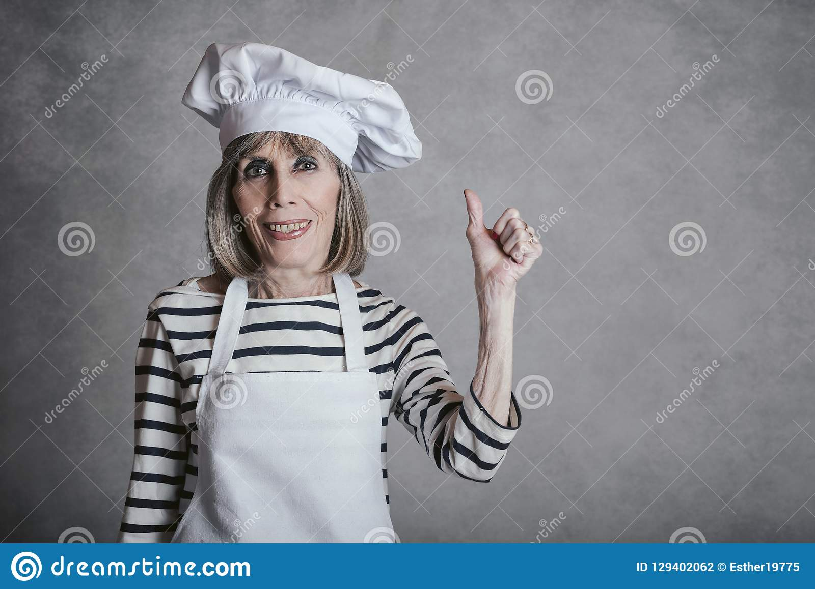 Smiling senior woman with cook hat. On gray background stock photography