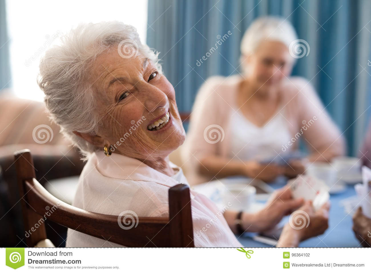 Smiling senior woman playing cards with friends