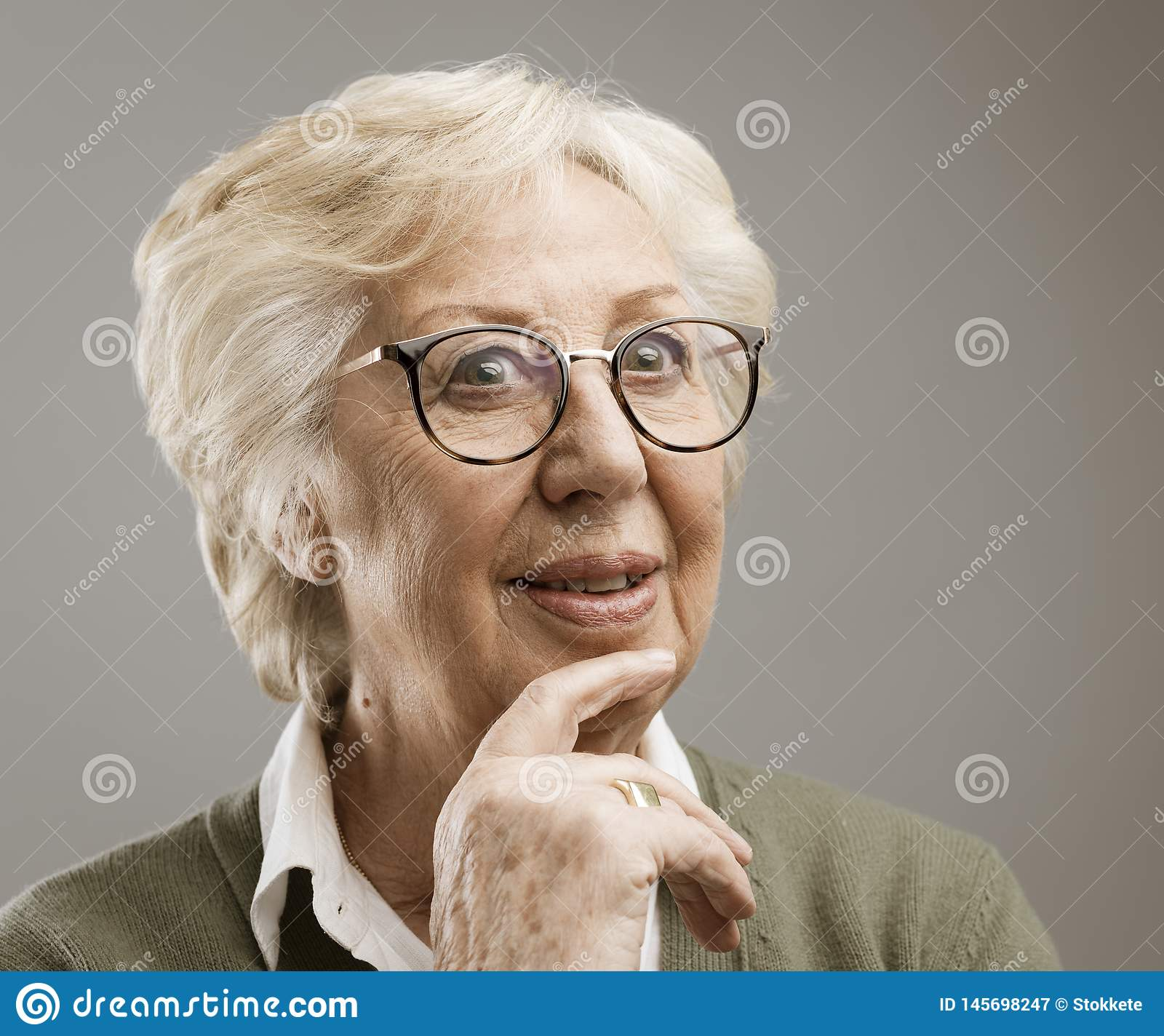 Smiling senior woman thinking with hand on chin