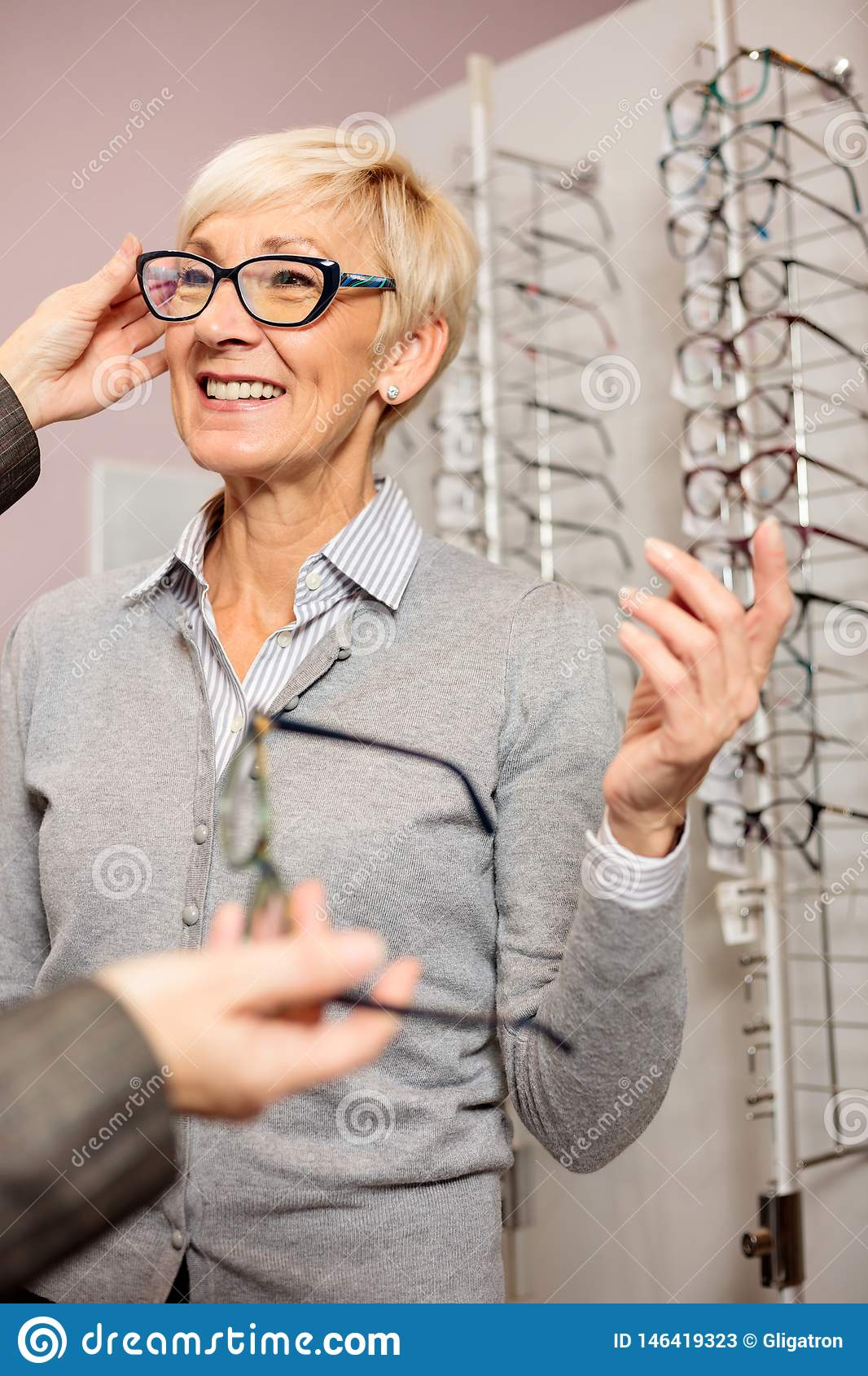Senior woman buying reading glasses in optical store