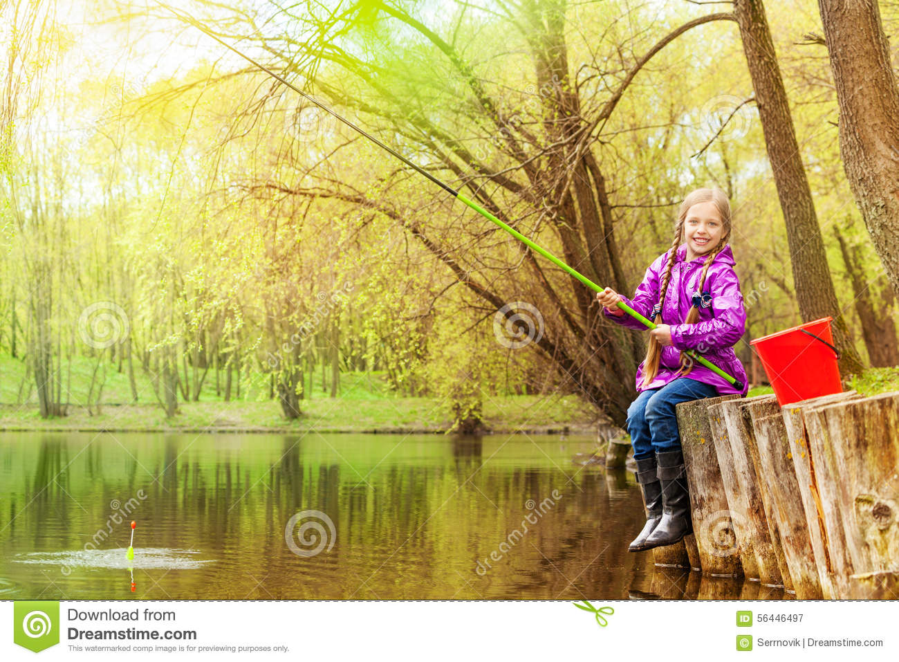Smiling small girl fishing near beautiful pond stock photo for Stocked fishing ponds near me