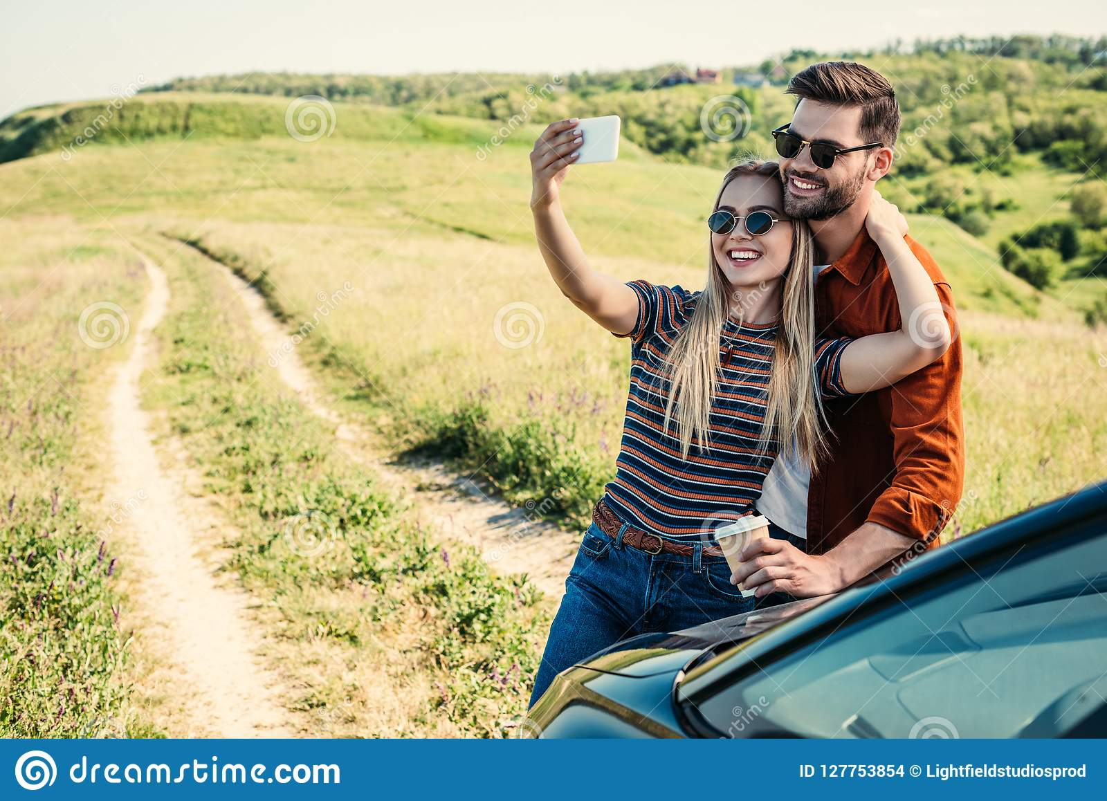 smiling stylish couple in sunglasses with coffee cup taking selfie on smartphone near car on rural