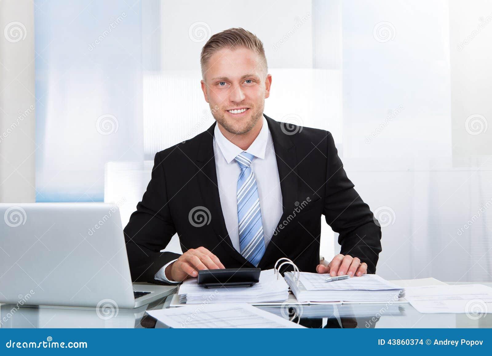 Smiling successful businessman st his desk