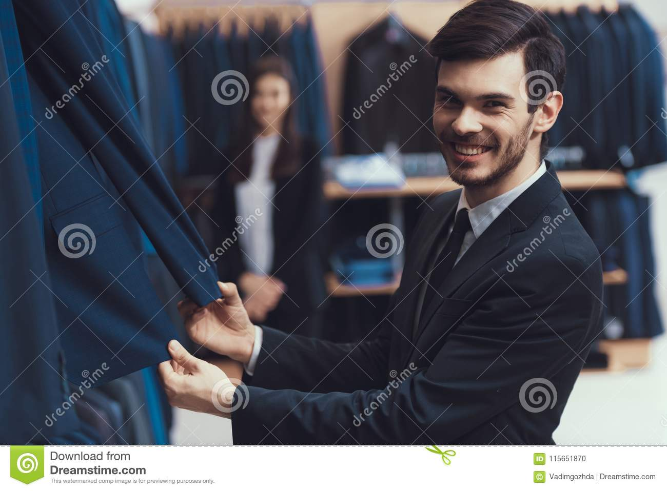 f1aec490 Smiling successful young man checks quality of jacket fabric in mens  clothing store.