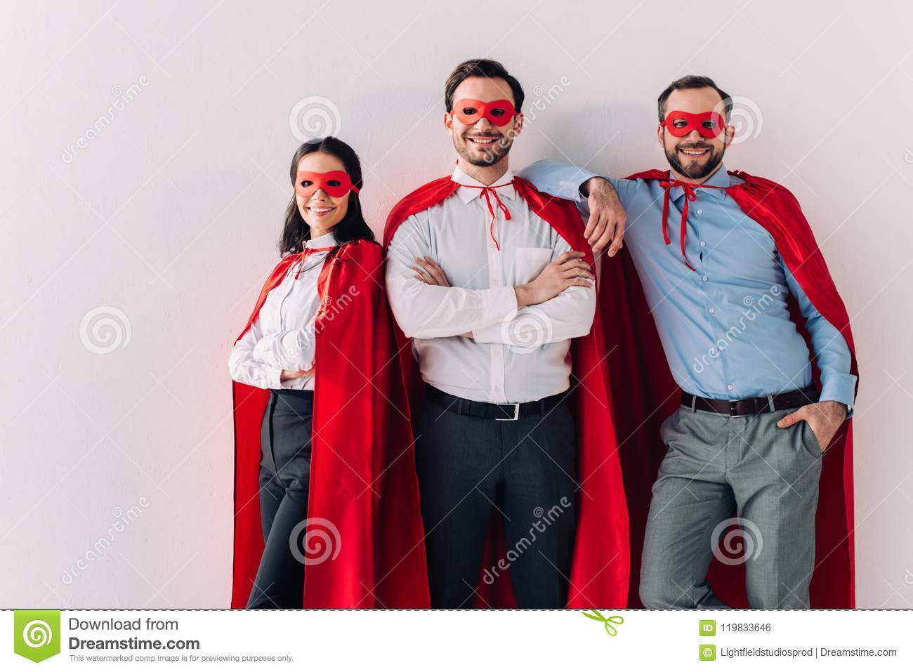 smiling super businesspeople in masks and capes looking at camera