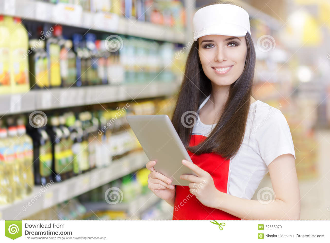 smiling supermarket employee holding a pc tablet stock