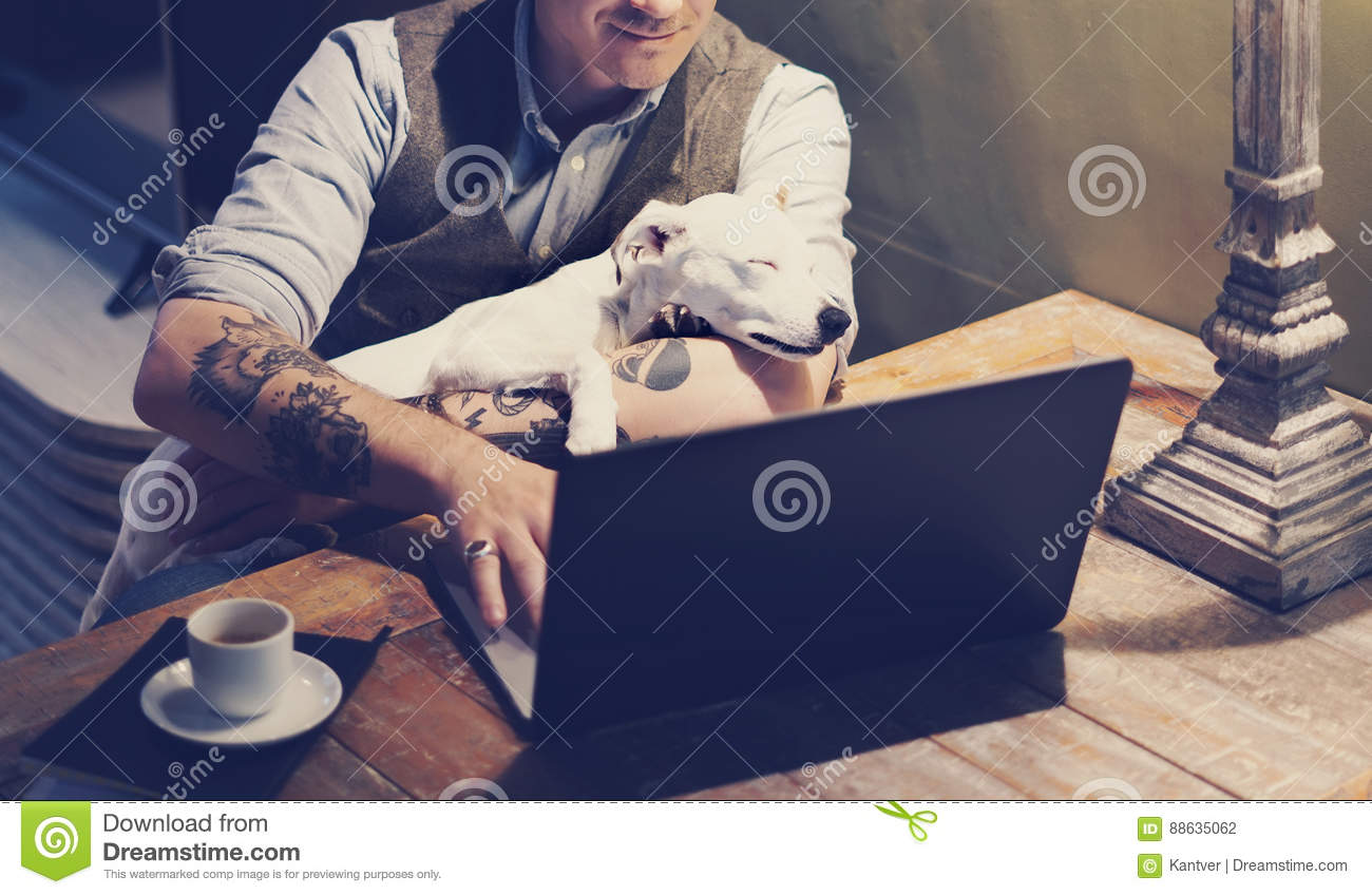 363f821d8 Smiling tattooed man in eyeglasses working at home on laptop while sitting  at the wooden table with cute dog sleeping on his hands.