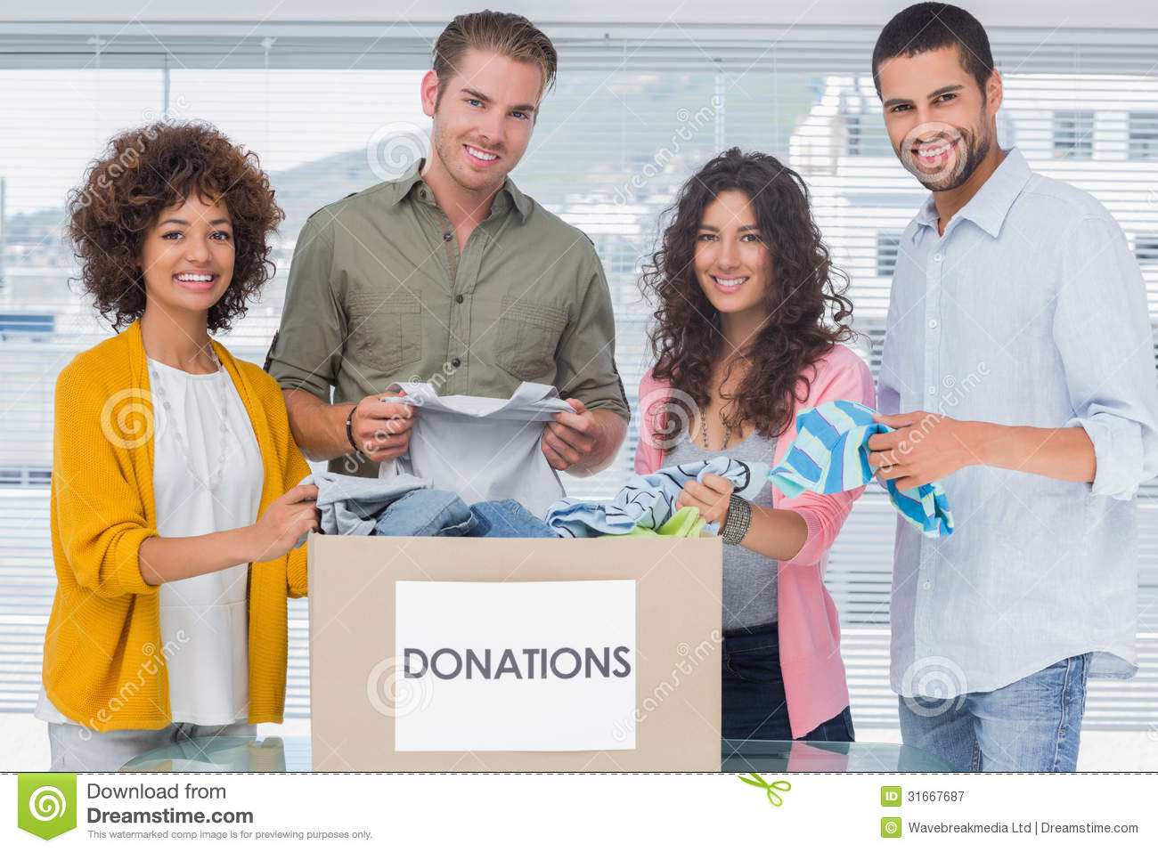 Smiling Team Of Volunteers Taking Out Clothes From A