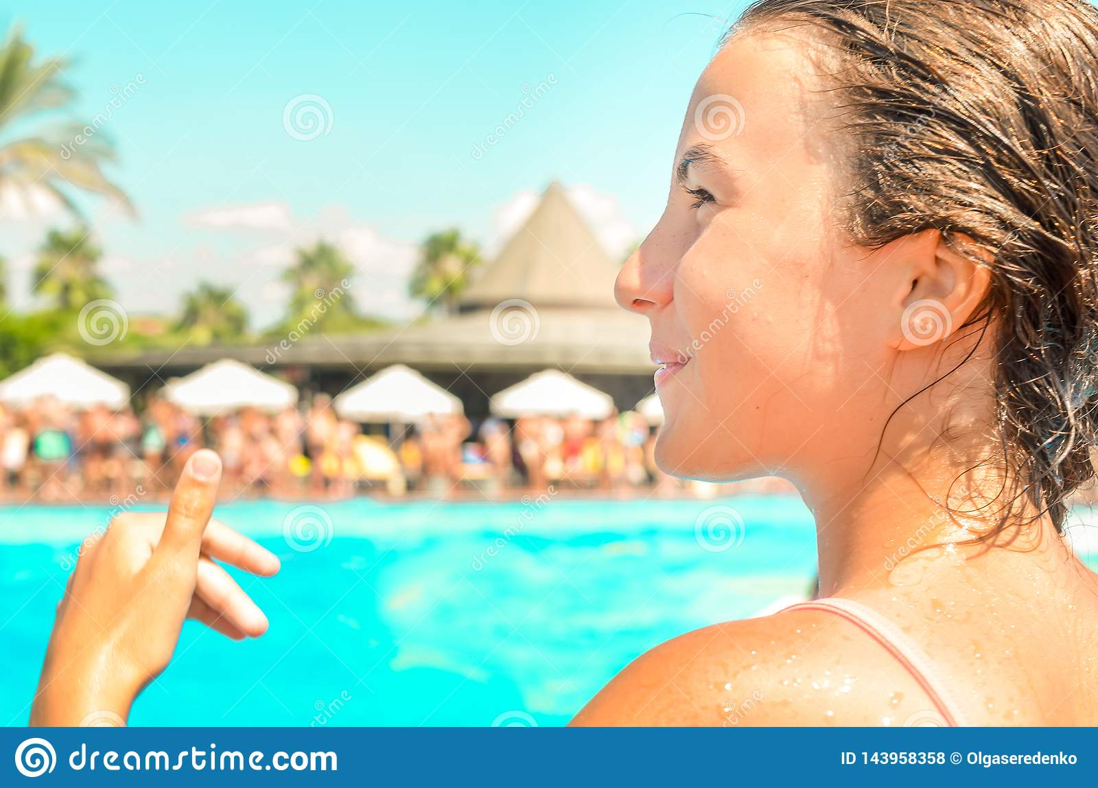 Smiling teen girl enjoing summer vacation at the hotel pool with palms and sun umbrellas on the background