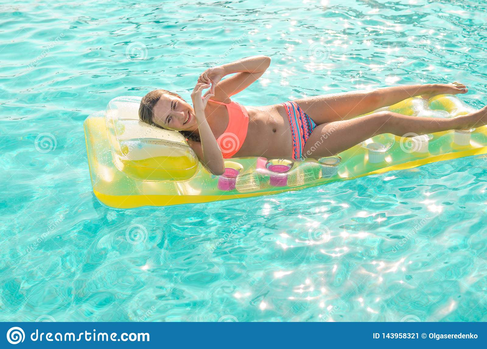 Smiling teen girl floating in the turquoise pool in bright coral bikini on a yellow mattress. Girl shows heart symbol