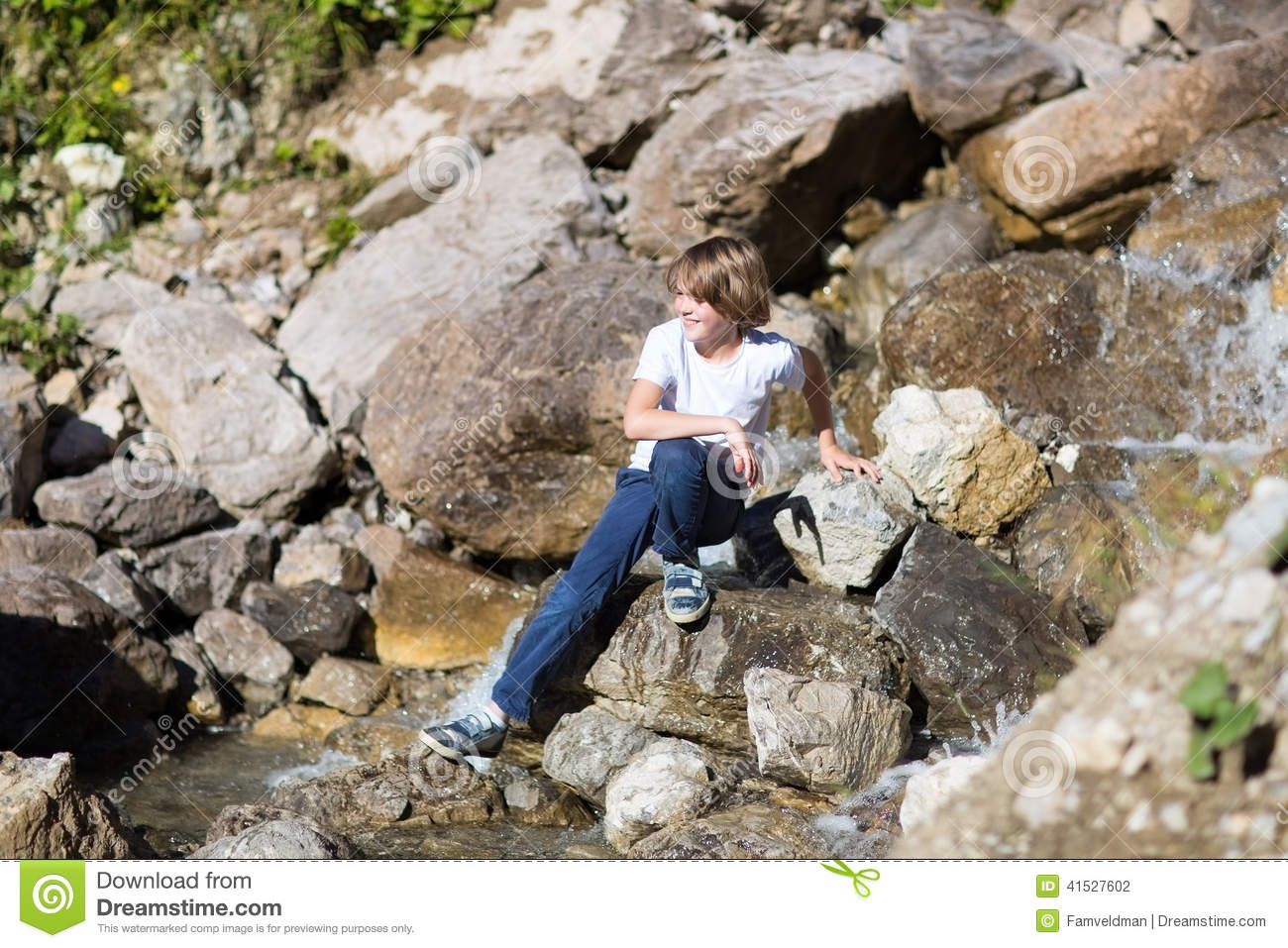 Smiling teenage boy next small river in mountains