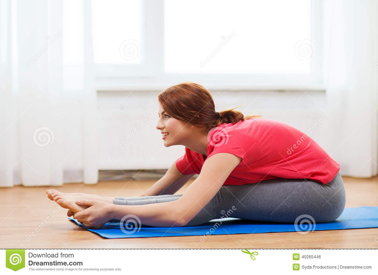 Smiling teenage girl streching on floor at home