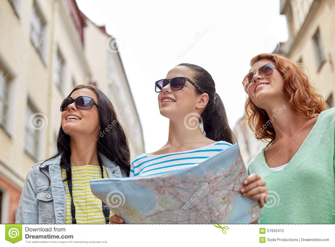 Smiling teenage girls with map and camera outdoors