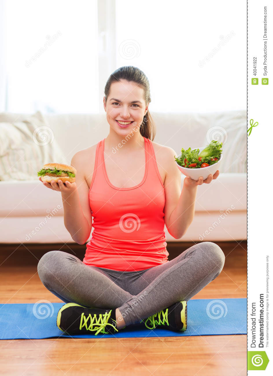 Smiling teenager with green salad and hamburger stock