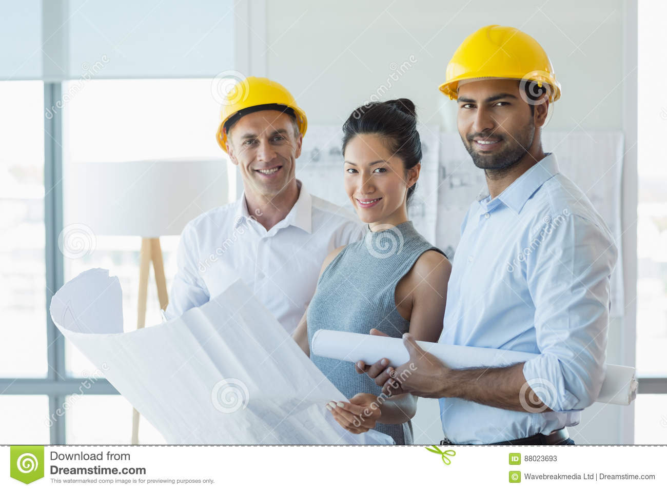 Smiling three architects standing in office with blueprint