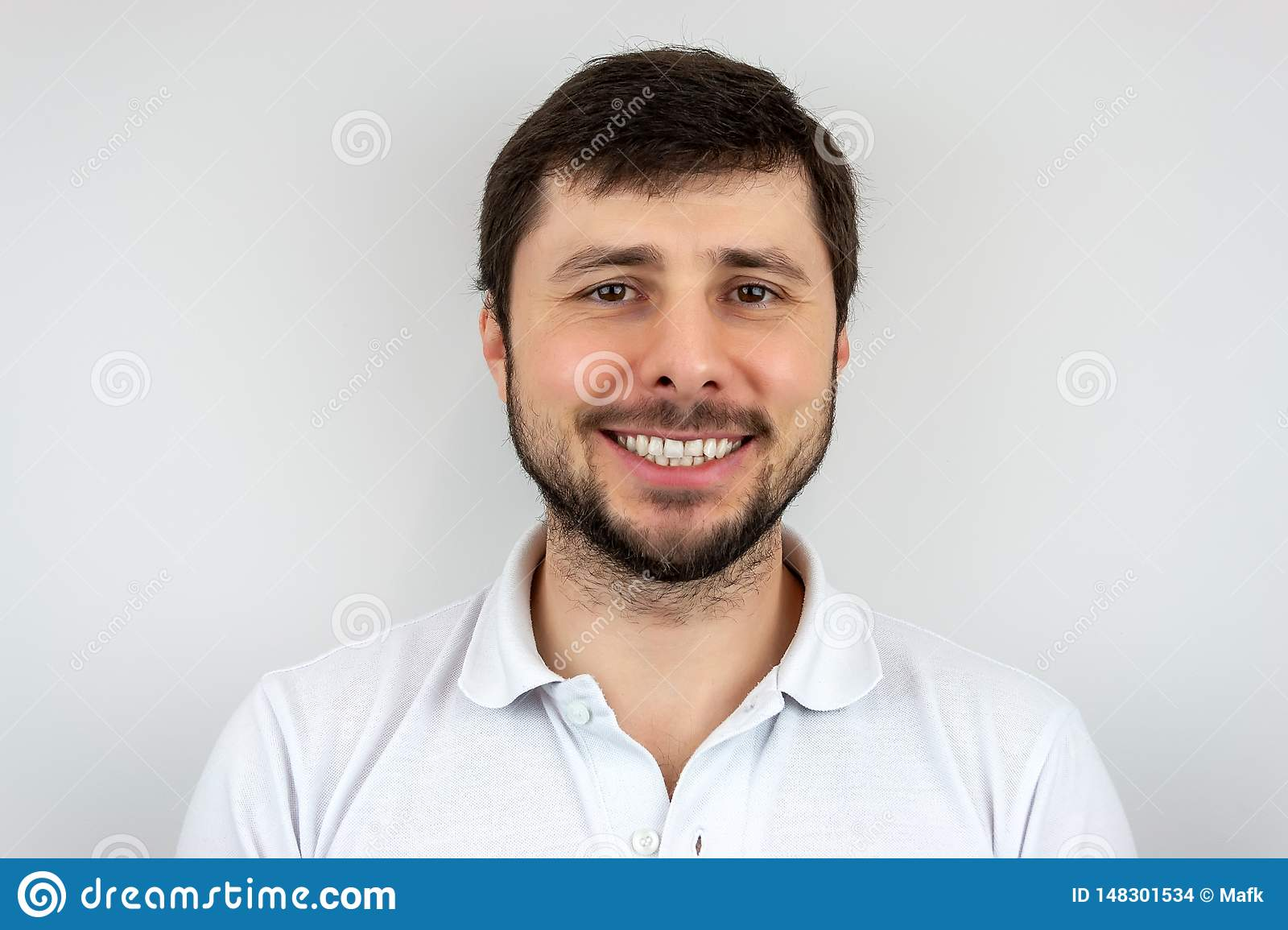 A smiling very happy handsome bearded man with brown eyes in a white t-shirt
