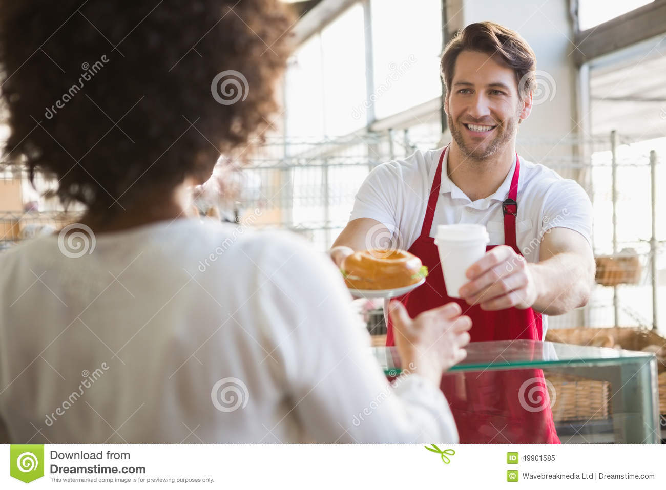 Smiling waiter giving lunch and hot drink to customer