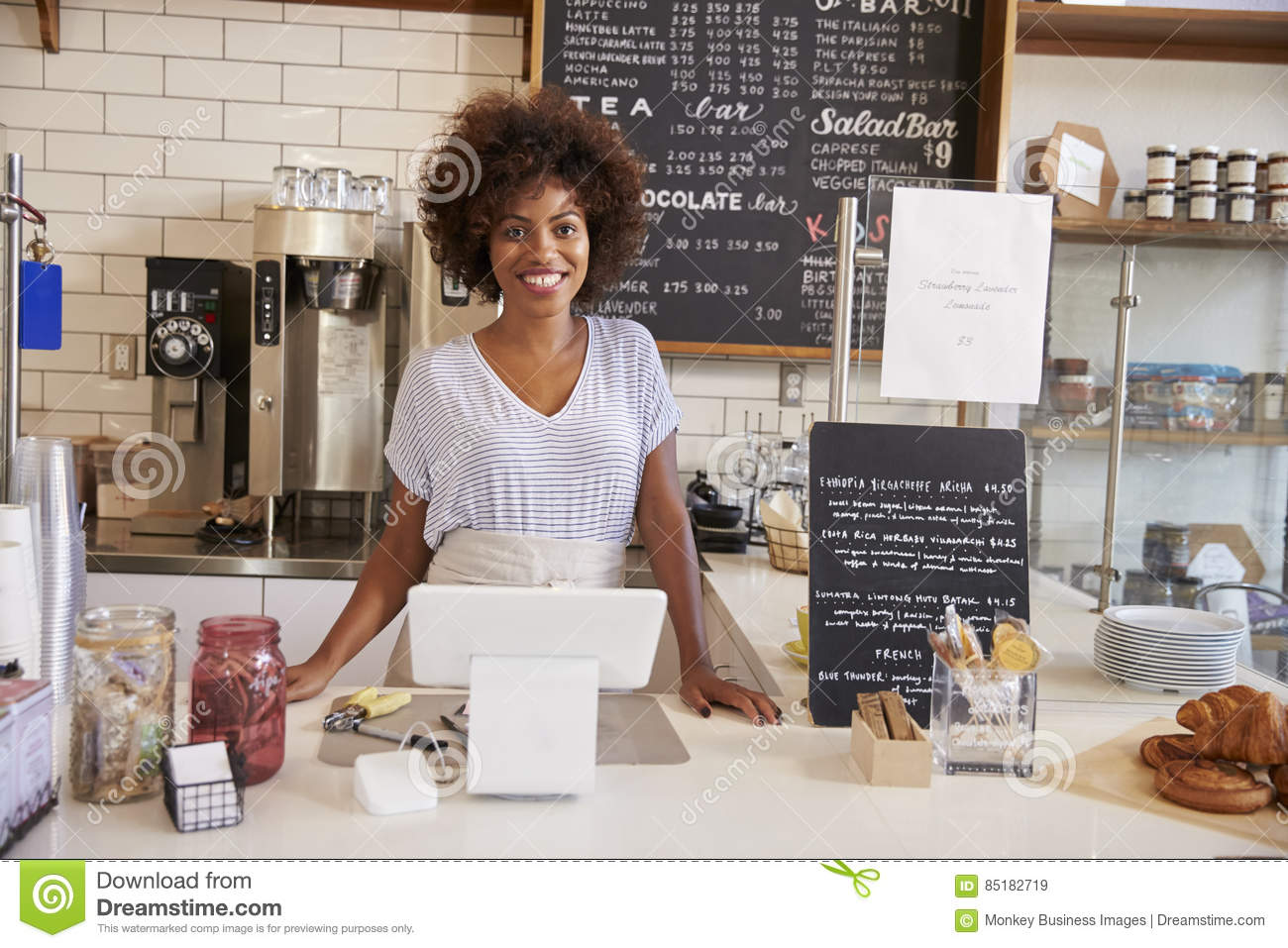 Smiling waitress behind counter at a coffee shop, close up