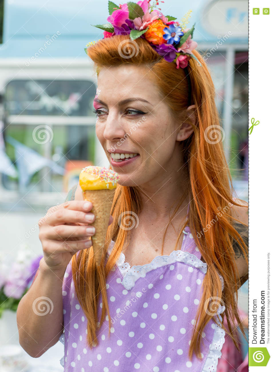 Smiling white lady wearing flower headband holding ice cream
