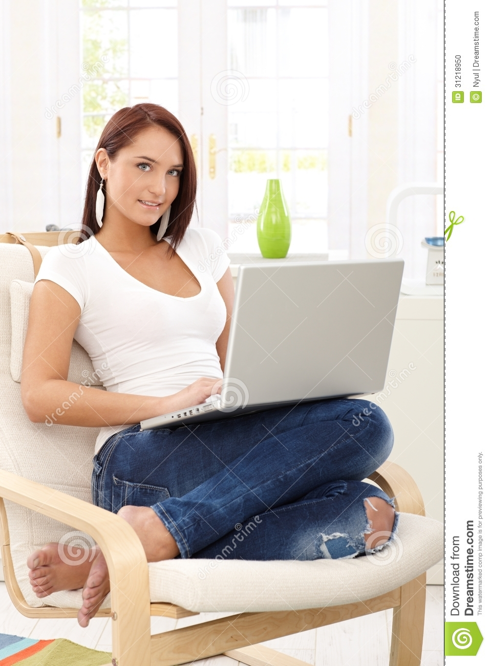 Smiling woman in armchair with computer stock photo for Sitting in armchair