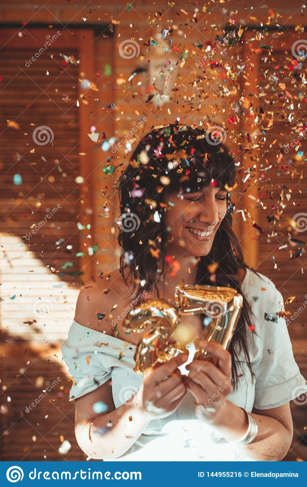 Smiling woman celebrating her 27th birthday with golden numbers and confetti