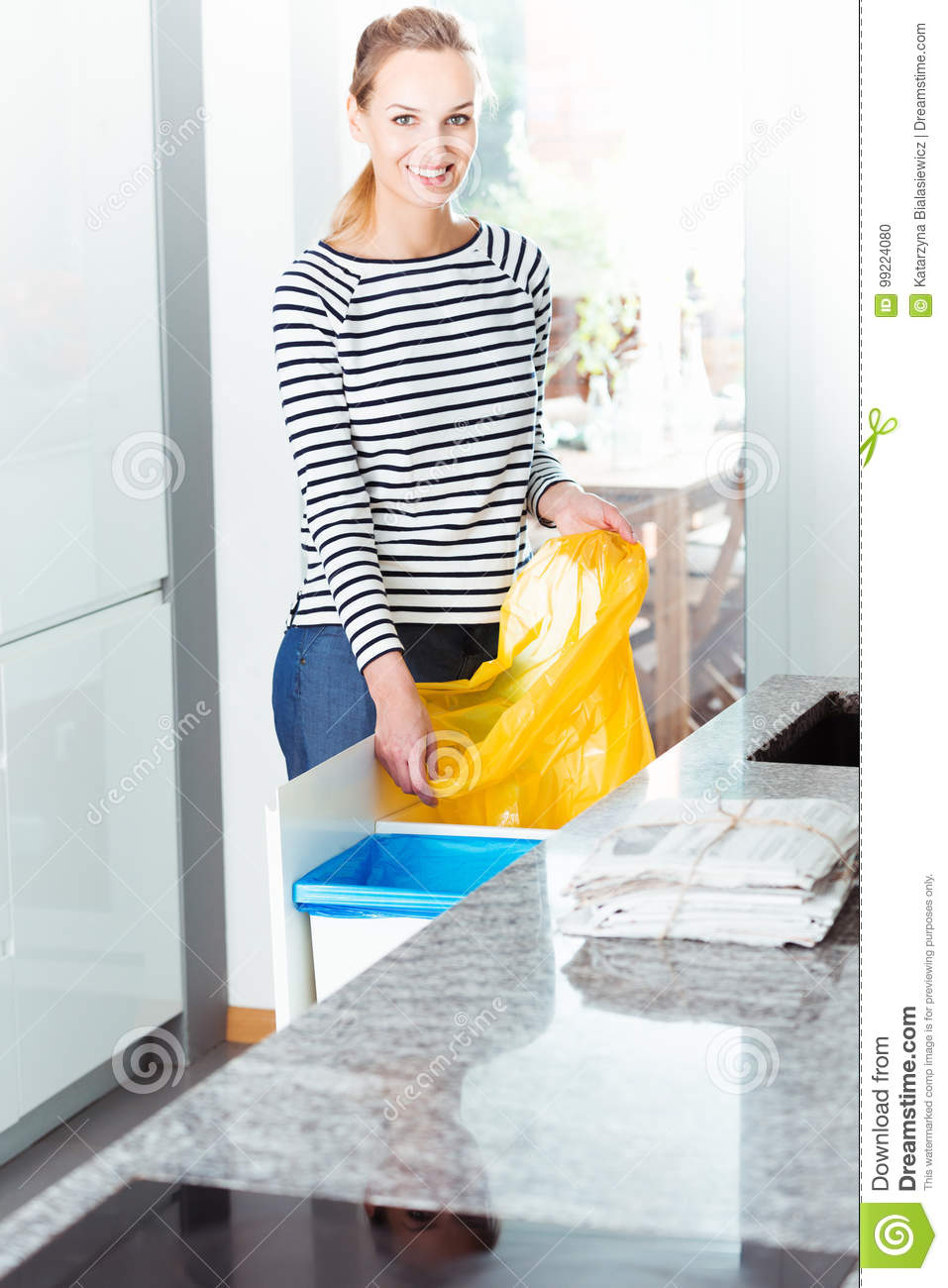 Woman changing bag for recycling