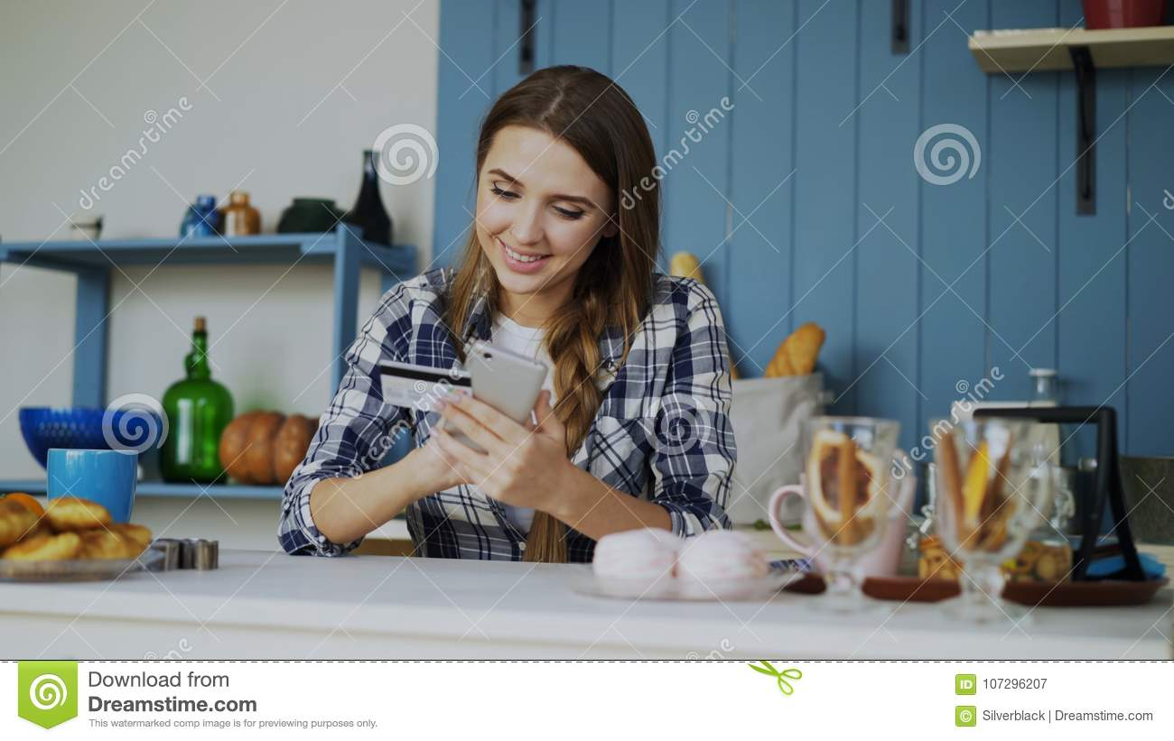 Smiling Woman Doing Online Shopping Using Smartphone And Credit Card ...
