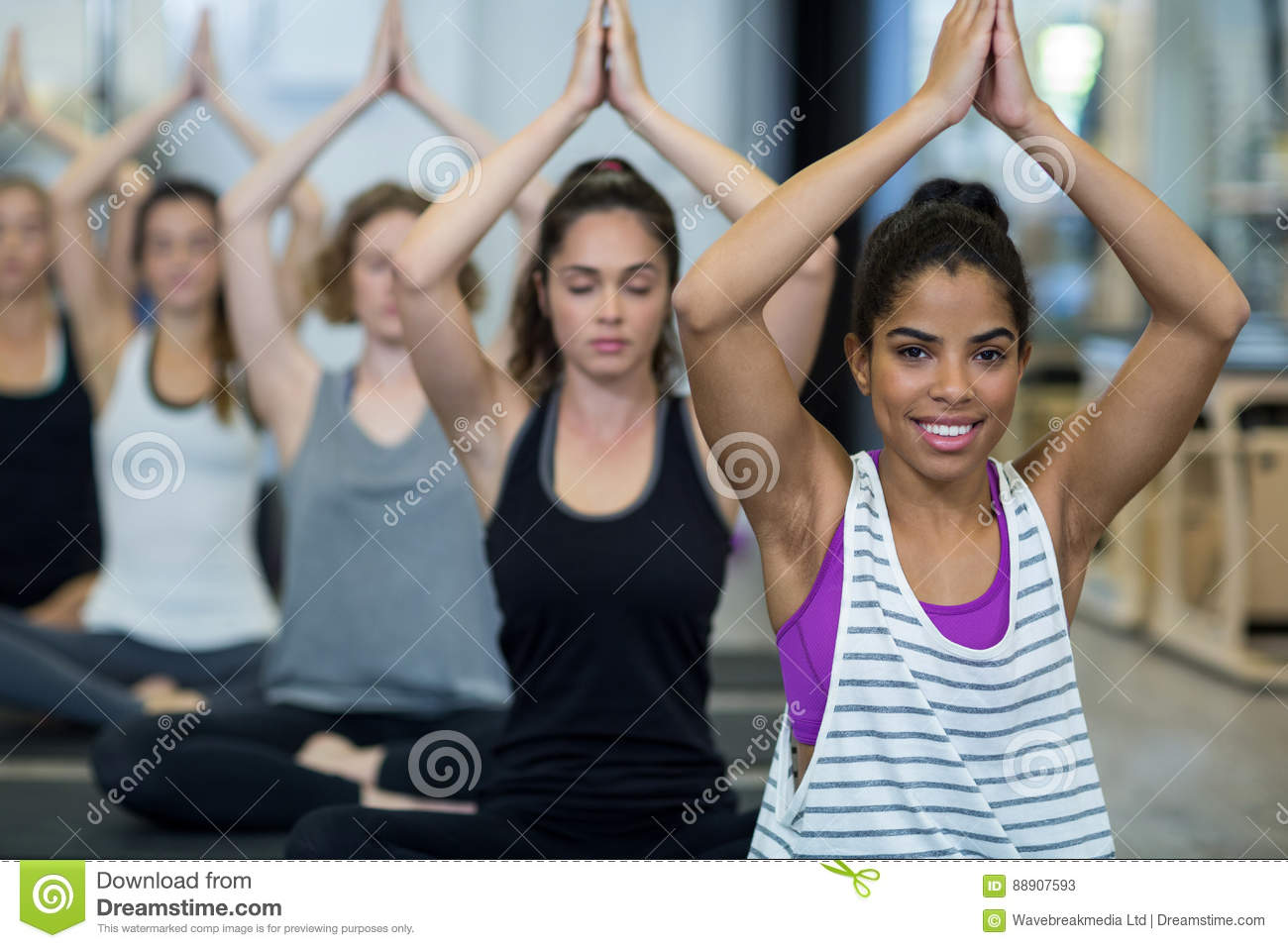 Smiling woman doing yoga in gym