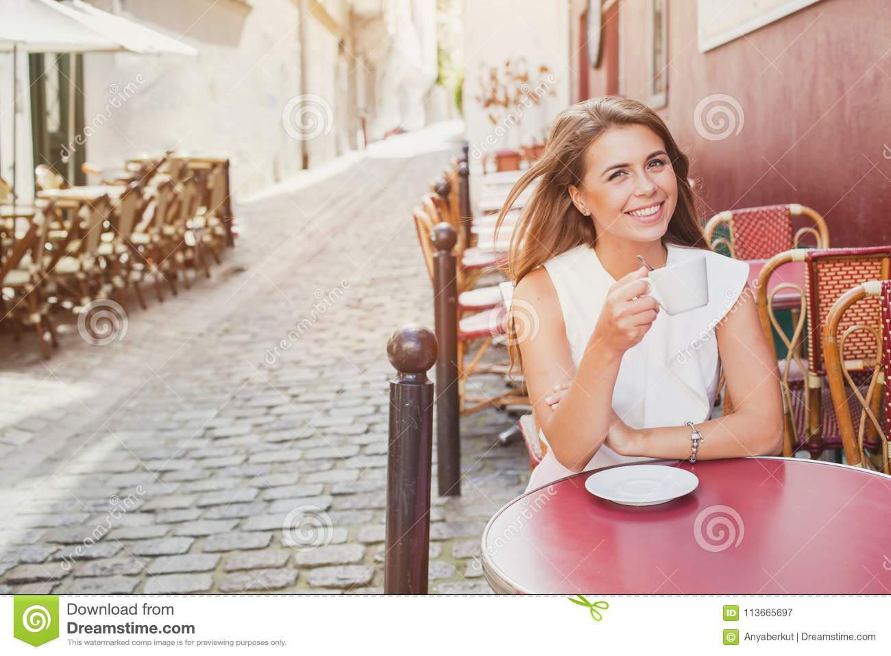 Smiling woman drinking coffee in street cafe