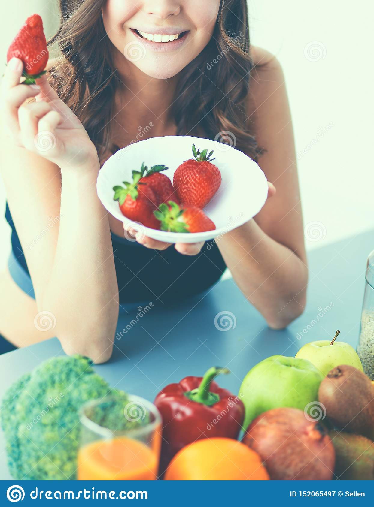 Smiling woman eating strawberry. Close up female face portrait