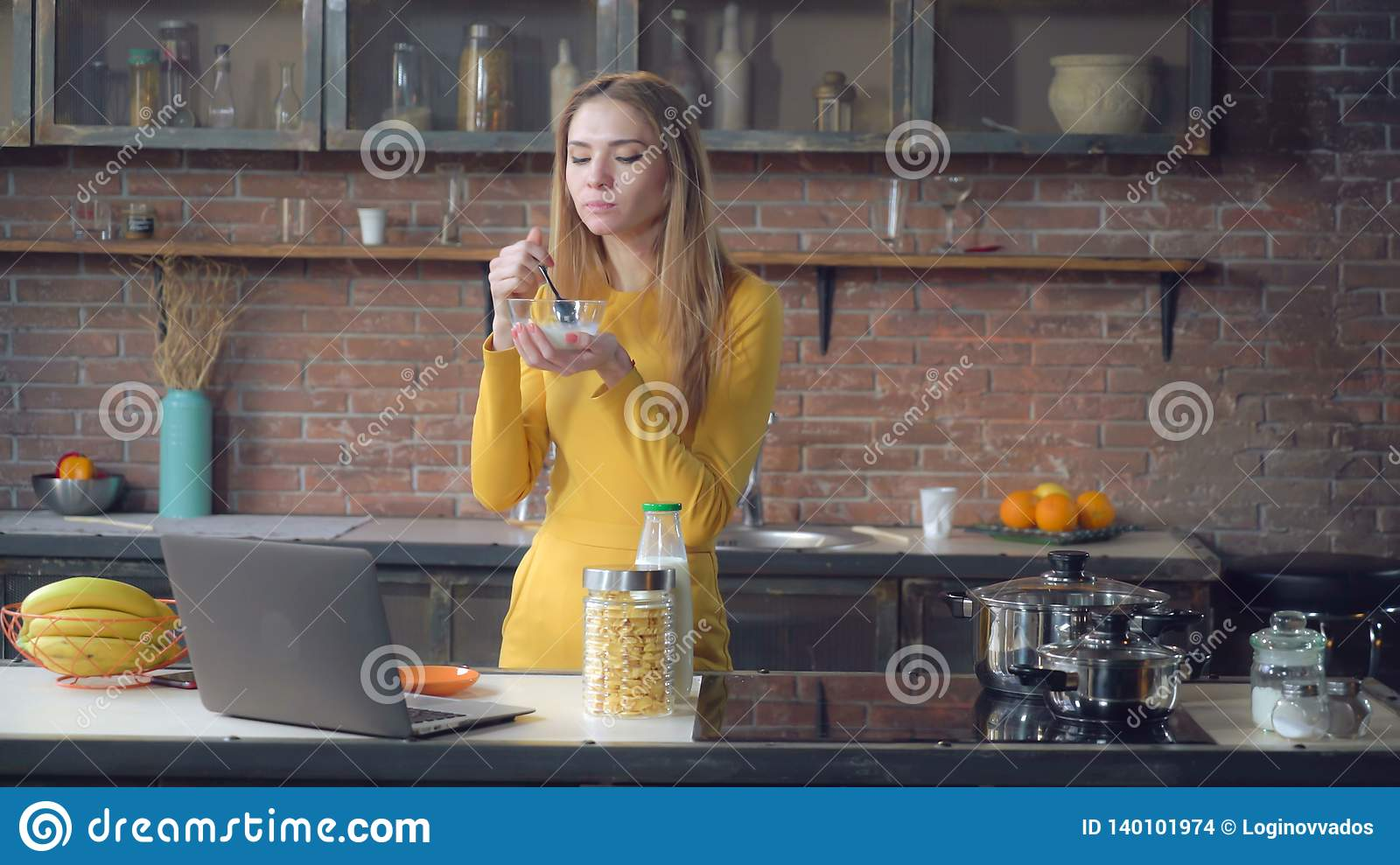 Lady eating in loft apartment with happy smile.