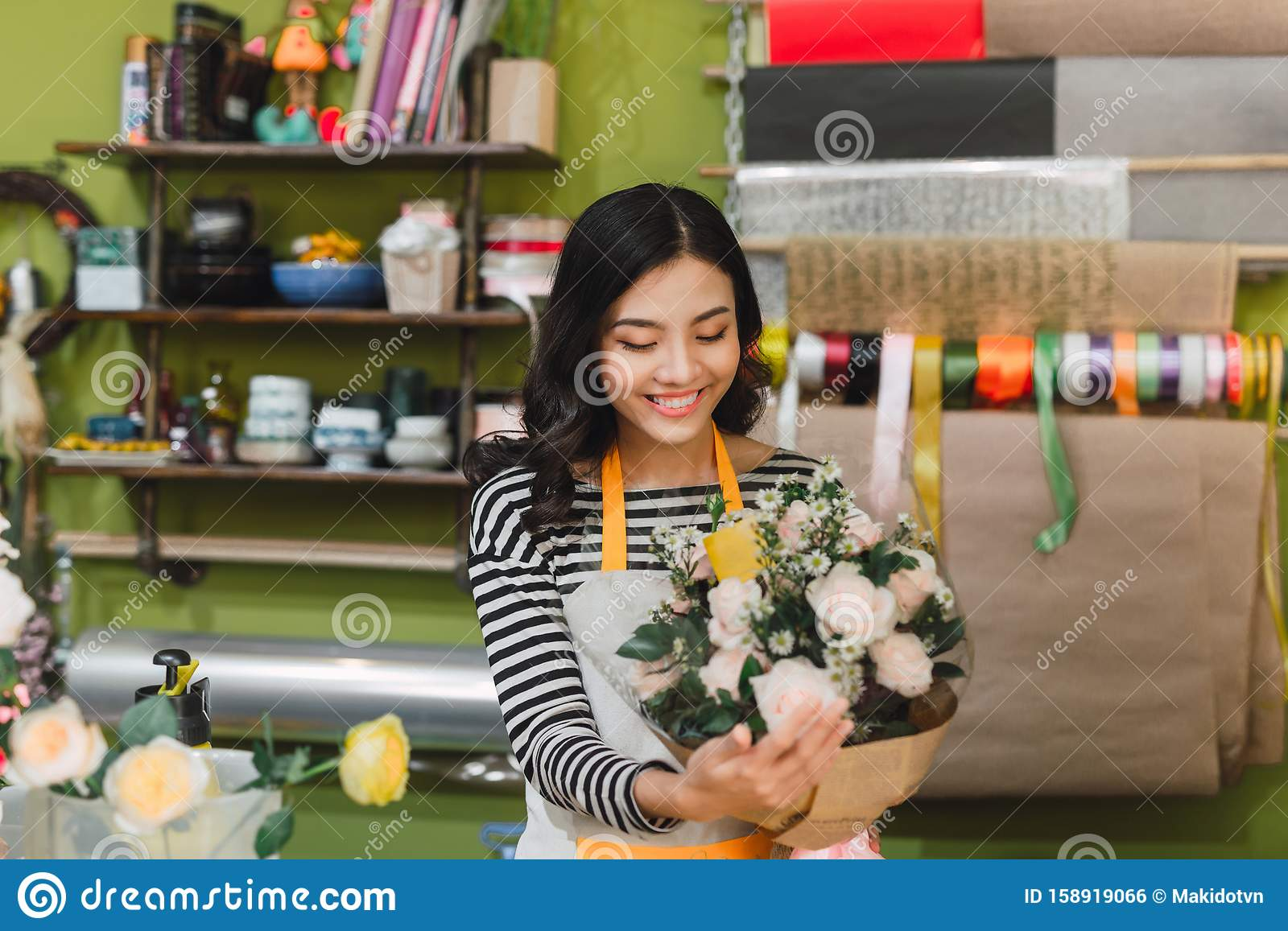Smiling woman florist, small business flower shop owner, at counter, looking friendly at camera working at a special flower