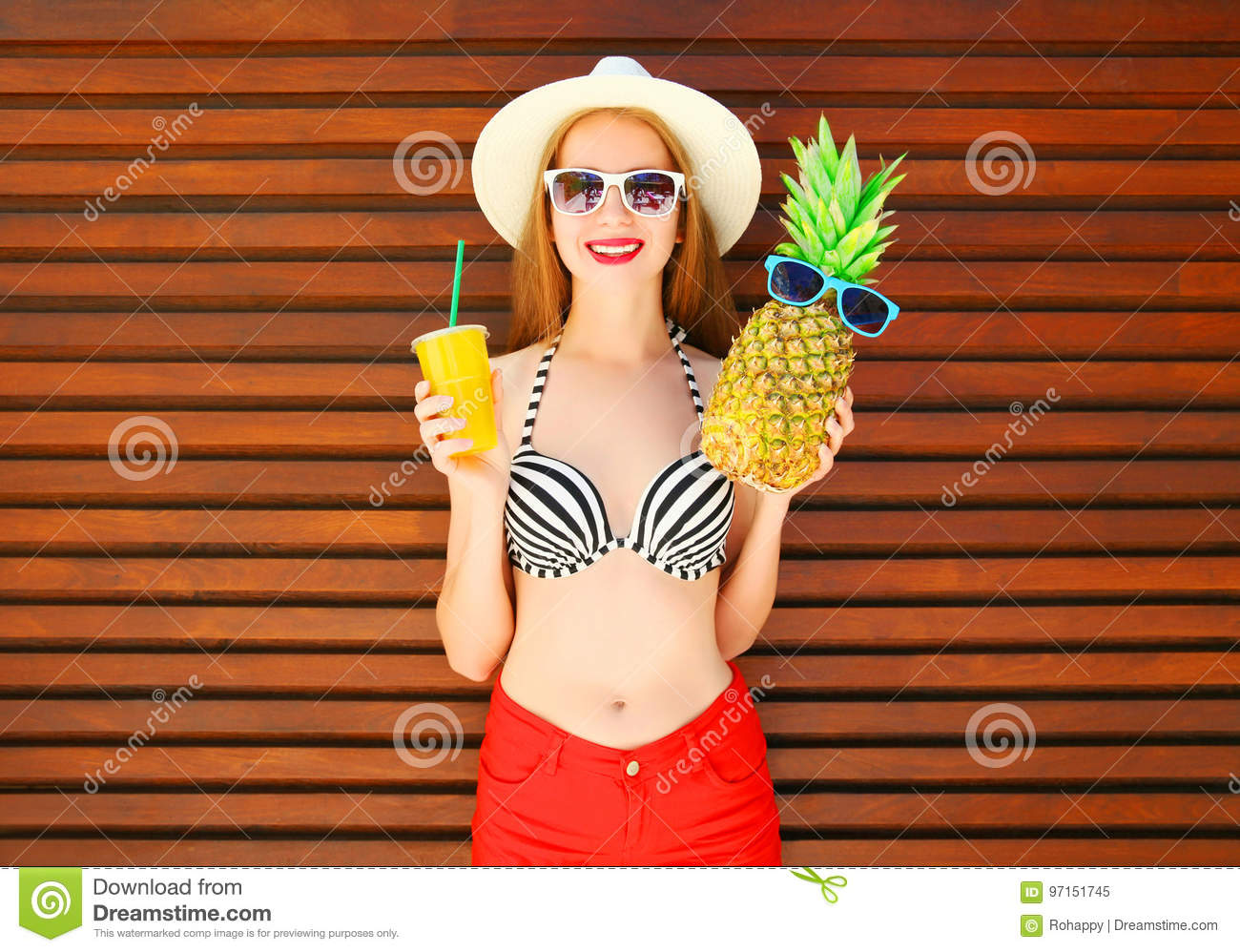 smiling woman with funny pineapple and juice cup or smoothies