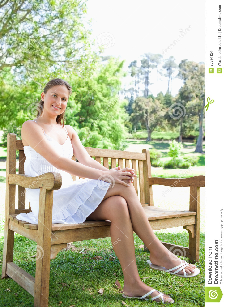 smiling woman with her legs crossed sitting on a park Weiss Park Newark DE Park Setting