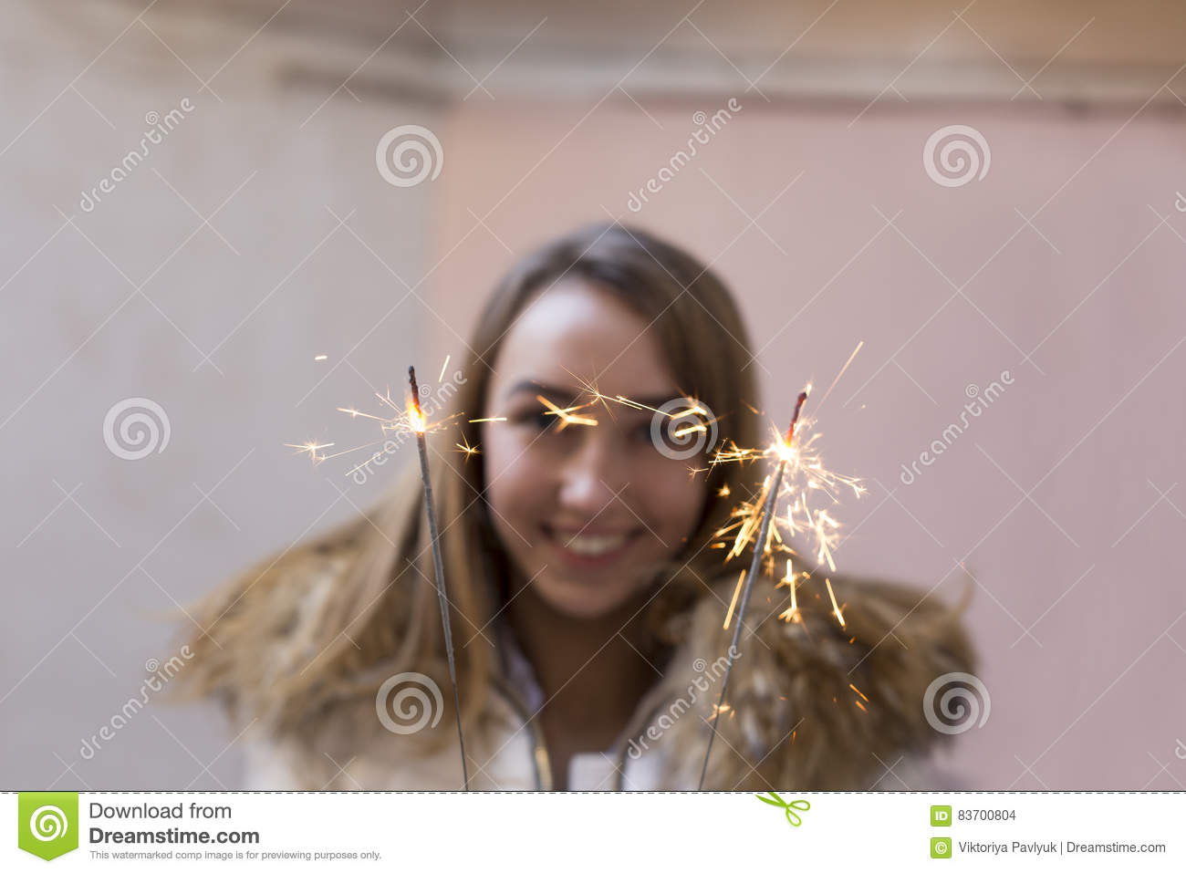 Smiling Woman Holding Bengal Lights. Blurred Background Stock Photo