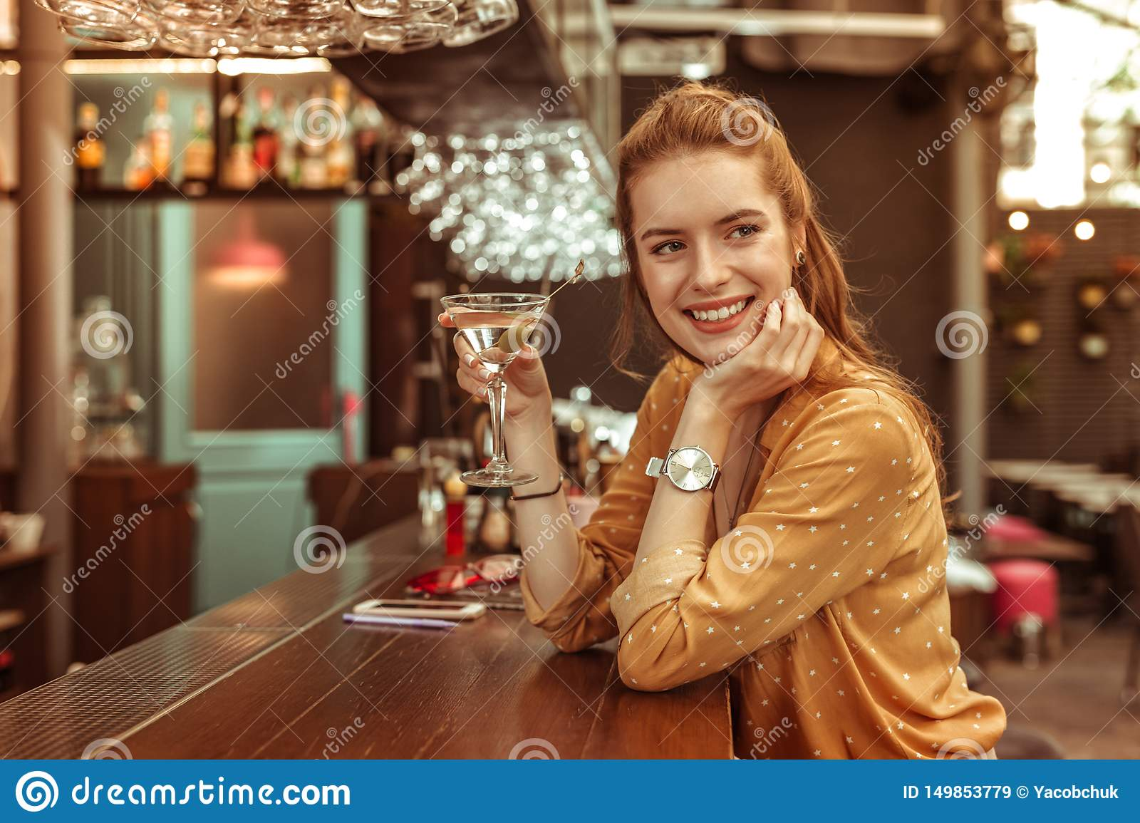 Smiling woman holding martini drink sitting at the bar counter