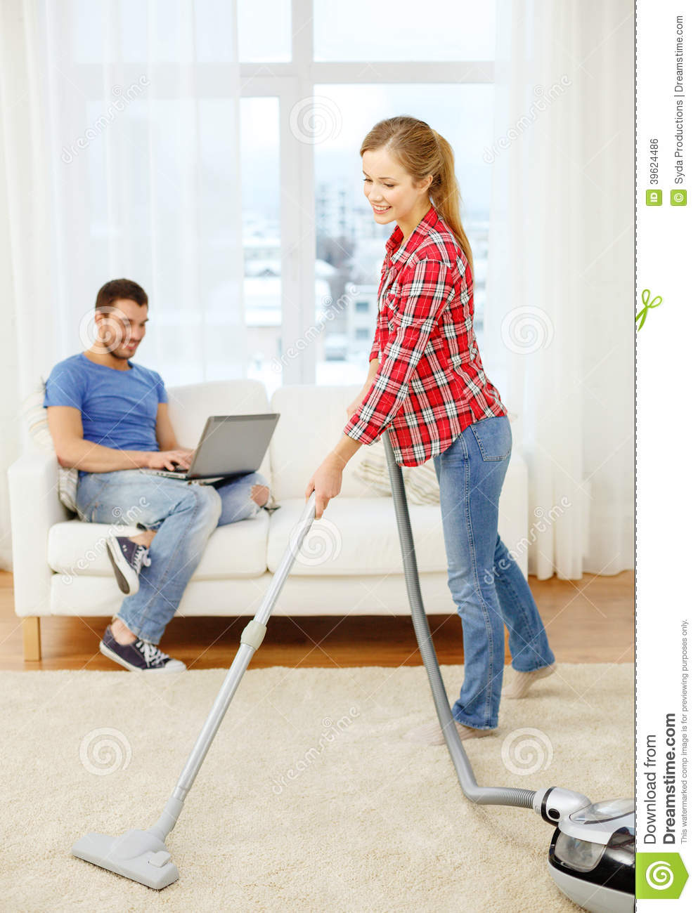 Smiling Woman With Hoover And Man Laptop Stock Photo