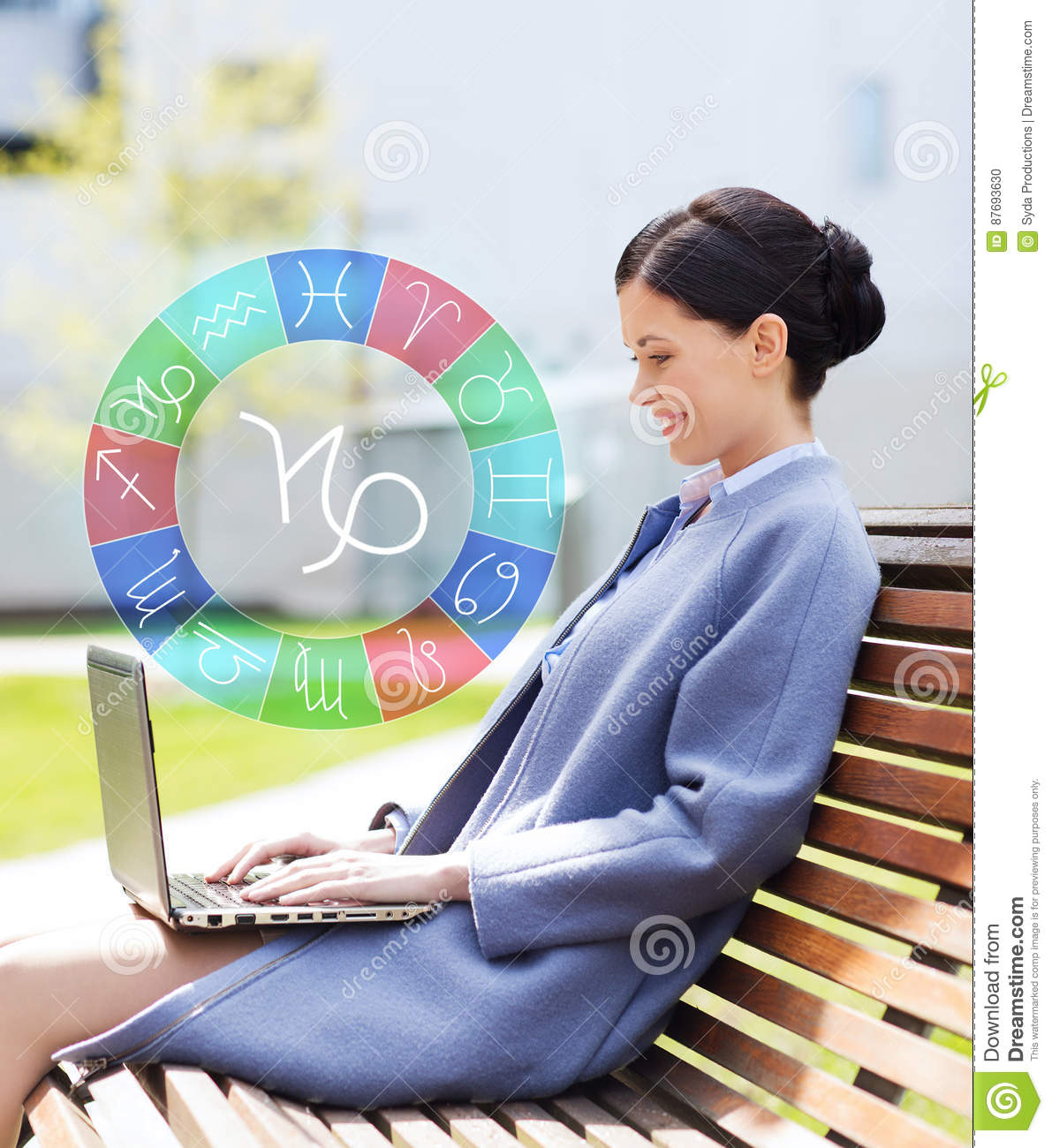 Smiling woman with laptop and zodiac signs in city