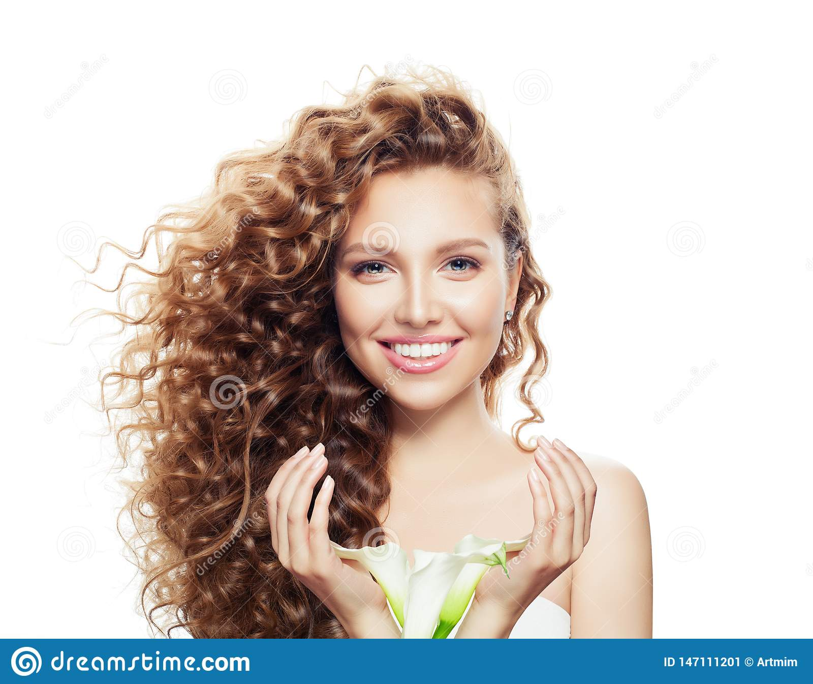 Smiling woman with long curly hair isolated on white. Beautiful model with clear skin and flowers in hands portrait