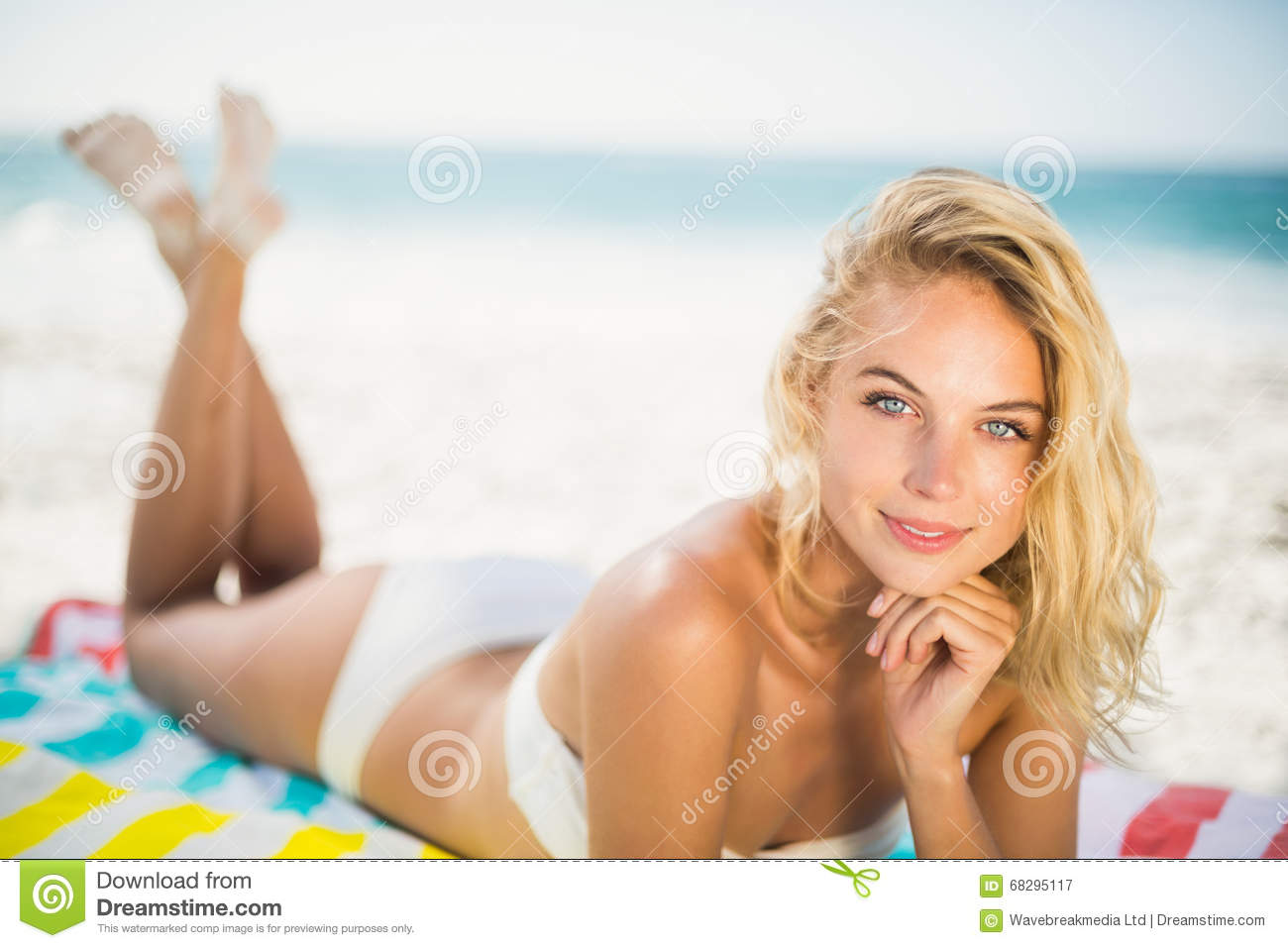 Smiling woman lying on a towel at the beach