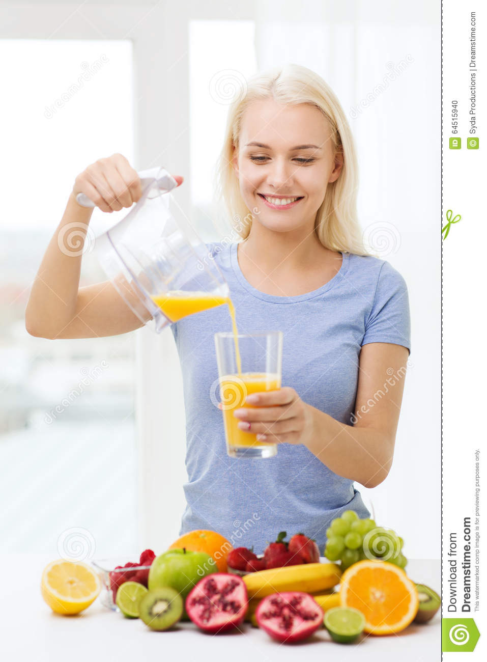 Smiling Woman Pouring Fruit Juice To Glass At Home Stock ...