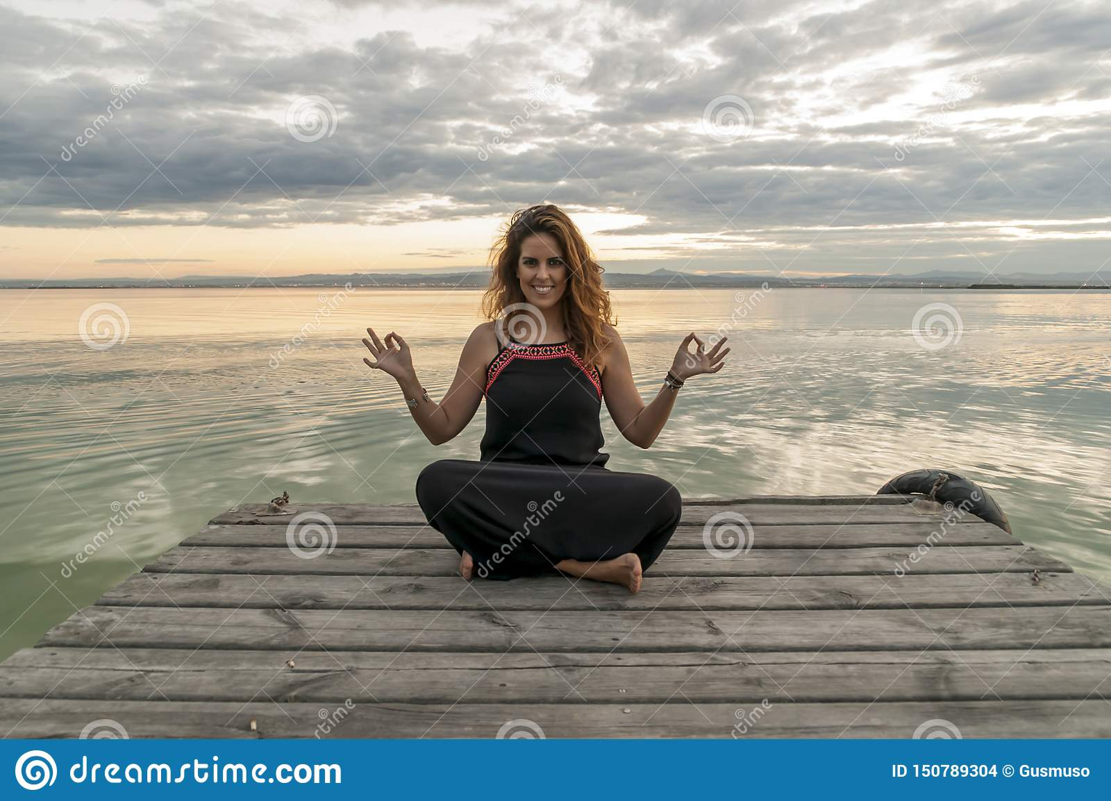 Smiling woman practicing meditation in the lotus yoga position on a wooden jetty